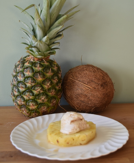 Boozy rotisserie pineapple with coconut ice cream all ready to be eaten