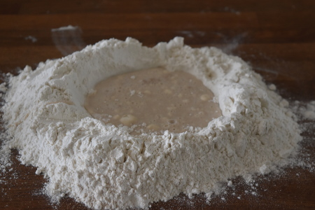 Making a flour well to bring together the vegan pesto pizza dough